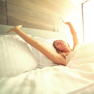 Young woman waking up in her hotel room, stretching arms