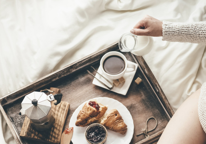 Woman having breakfast in bed. Window light