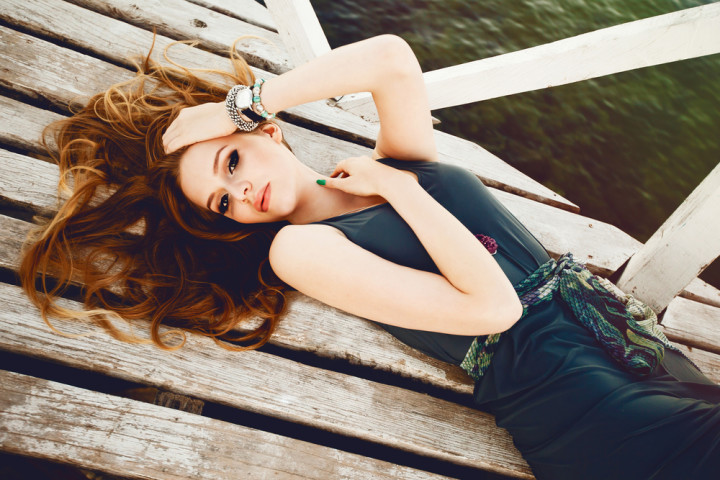 young model laying at the beach in wooden floor