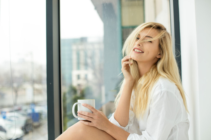 beautiful blonde woman sitting comfortably on a balcony
