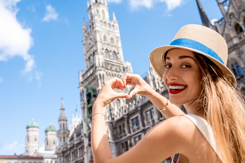 Young female tourist making heart shape with hands