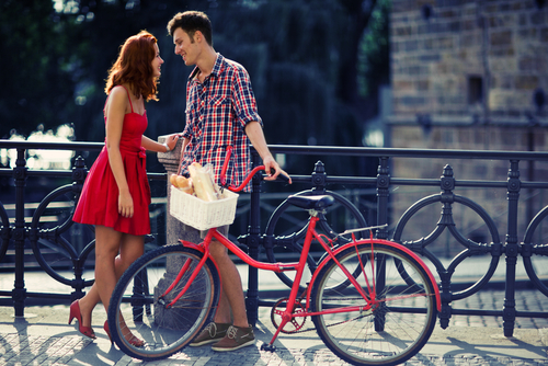Couple in Red Walking on the Street with Bike