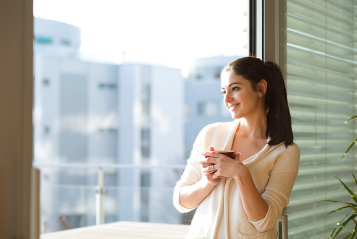 Woman relaxing on balcony holding cup of coffee