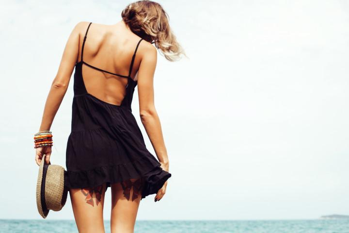 Woman in black back-bearing dress holding fedora on a beach