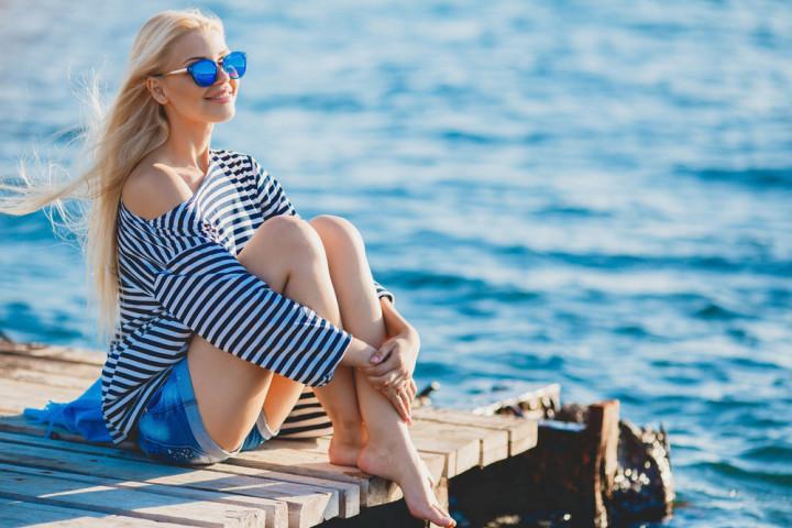Beautiful Girl in sea style sitting on wooden bridge