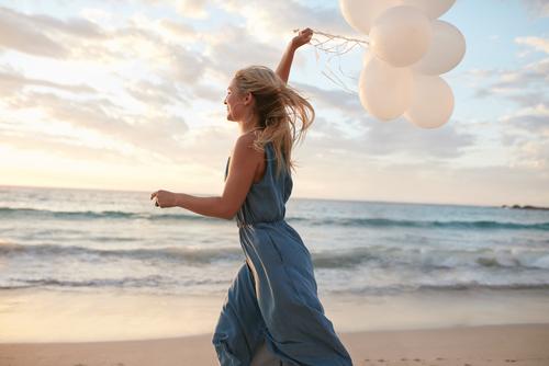 風船を持って海辺を走る女性
