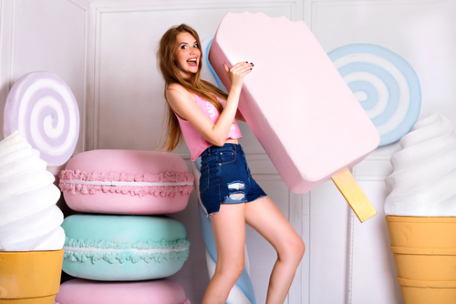 blonde girl holding big props pink ice cream
