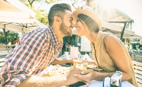 Couple in love kissing at bar eating local delicacie