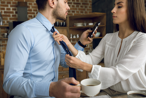 businesswoman helping husband tying tie