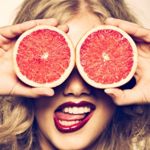 funny-portrait-girl-holding-red-grapefruit-infront-of-her-face-picture-id161961914