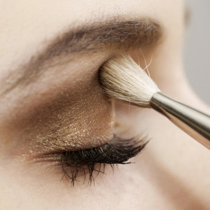 Close-up of woman putting golden makeup on her eye lid
