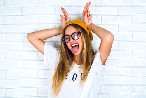 cheerful blonde hipster girl going crazy making funny face