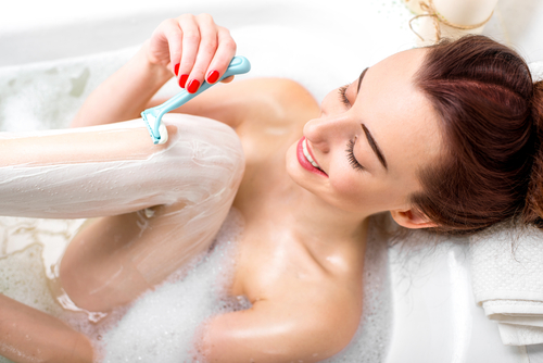 Young woman shaving her legs in the bath