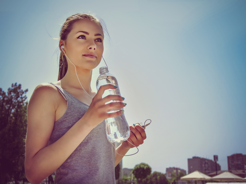 Girl is engaged in sports and drinking water