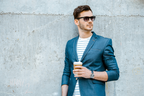 Man wearing jacket, sunglasses, shirt and holding cup of coffee