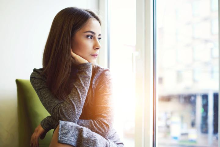 窓の向こうを見る女性