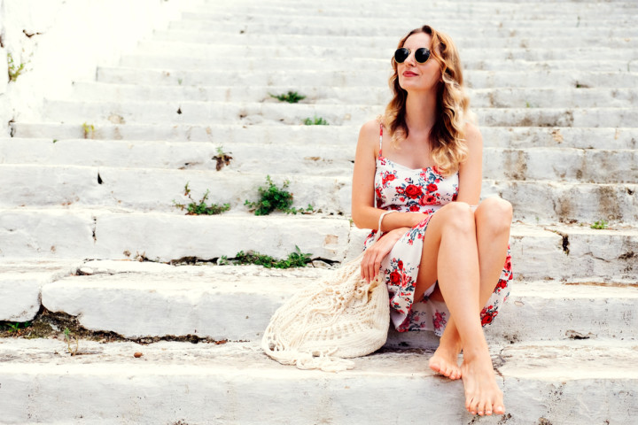 young woman in dress sitting on steps