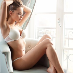 young-blond-woman-in-underwear-sitting-next-to-the-window-picture-id466334724