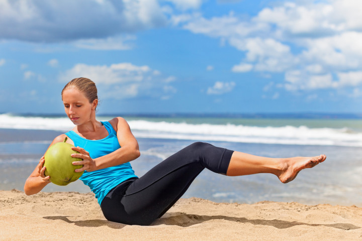 Woman fitness exercise with green coconuts on ocean beach