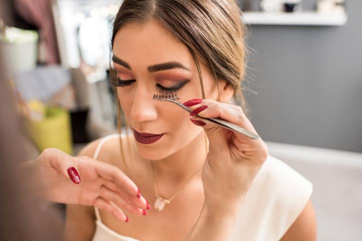 Unrecognizable beautician applying false eyelash in beauty salon.