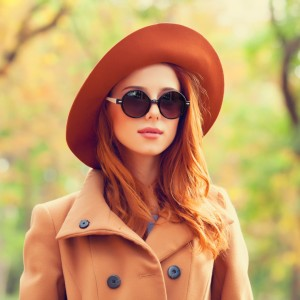 redhead-girl-in-sunglasses-and-hat-in-the-autumn-park-picture-id517997267