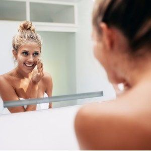 smiling-woman-reflection-applying-face-cream-picture-id629599938