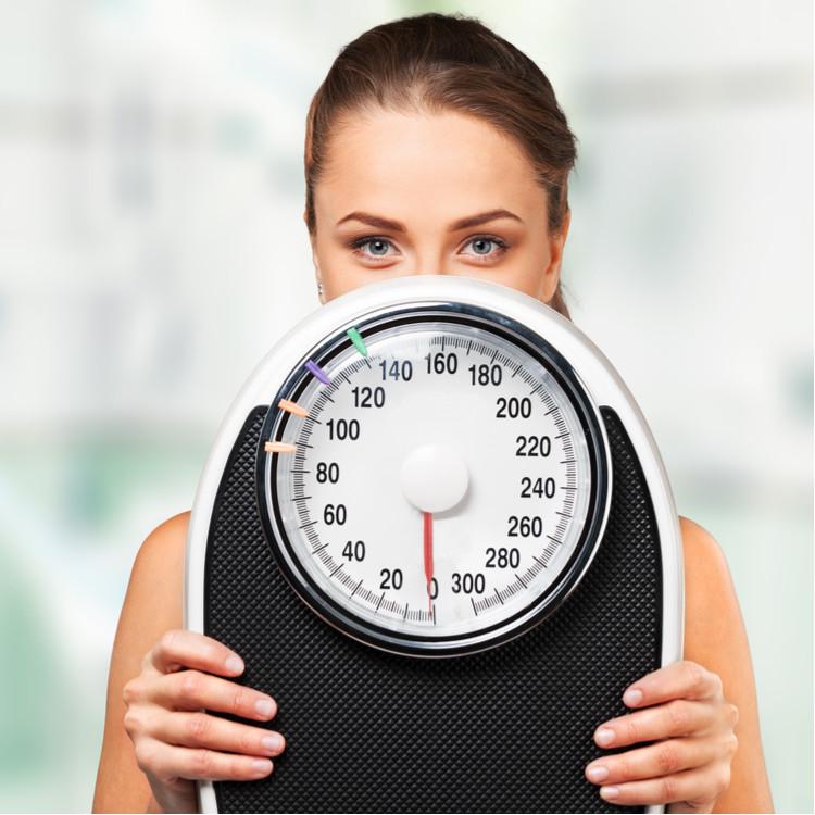 体重計を持つ女性