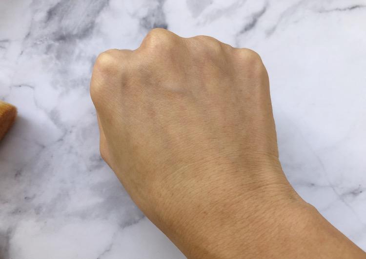 手の甲で余分な粉を払う