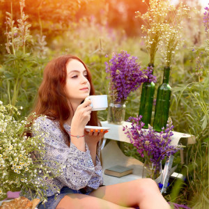 Young,Girl,Holds,White,Cup,With,Summer,Flowers,And,Herbs