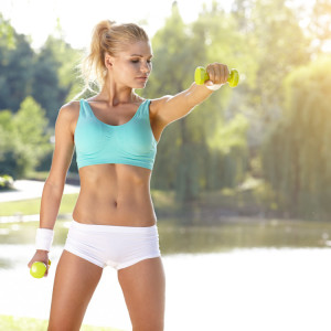 Fitness,Instructor,Exercising,With,Small,Weights,In,Green,Park